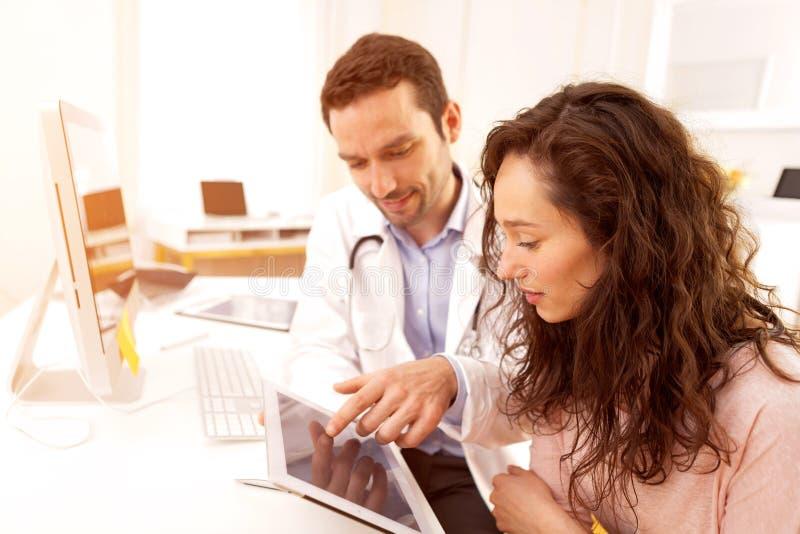 Arts die tablet gebruiken om patiënt te informeren stock foto's