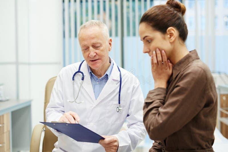 Arts die testresultaten verklaren aan patiënt stock foto