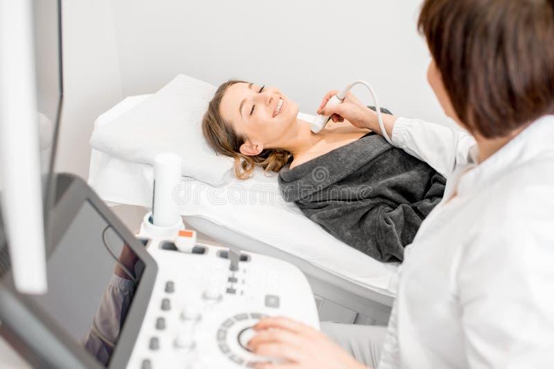 Arts die ultrasone klank tot onderzoek maken aan een jonge vrouw stock afbeeldingen
