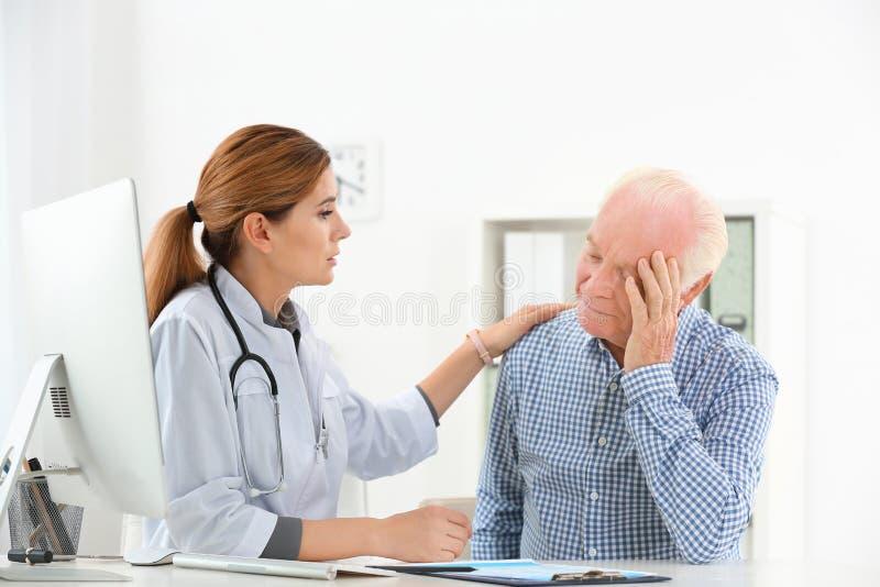 Arts die verstoorde bejaarde patiënt troosten stock foto's