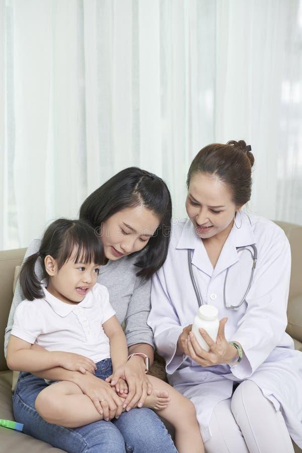 Arts die vitaminen voorschrijven aan kind stock foto