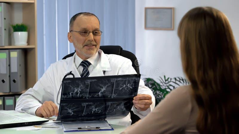 Arts die vrouwelijke patiënt informeren over goede resultaten van schepenröntgenstraal, terugwinning stock afbeelding