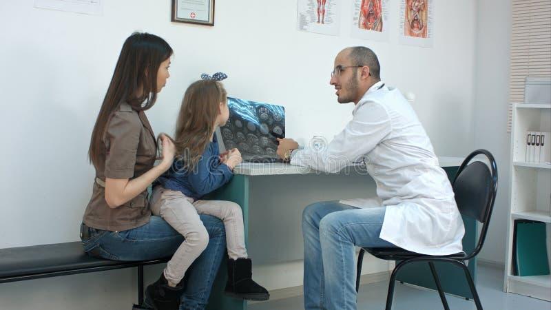 Arts die xray beeld tonen aan jonge moeder met vrolijke dochter stock foto