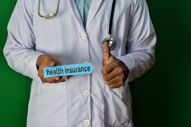 Arts die zich op Groene achtergrond bevinden Houd de Ziektekostenverzekeringdocument tekst stock afbeelding