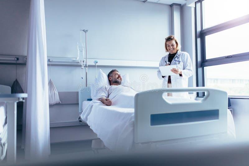 Arts die zieke patiënt in het ziekenhuisbed bijwonen stock foto's