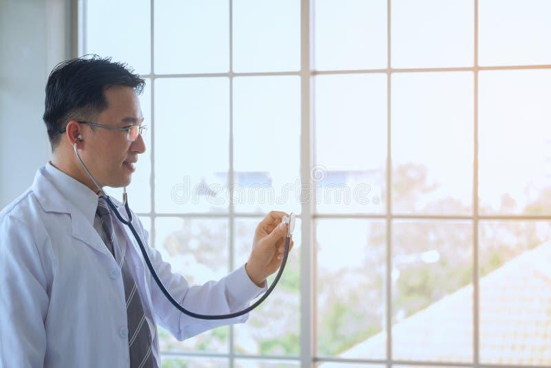 Arts in een peignoir met een stethoscooponderzoek in stock foto