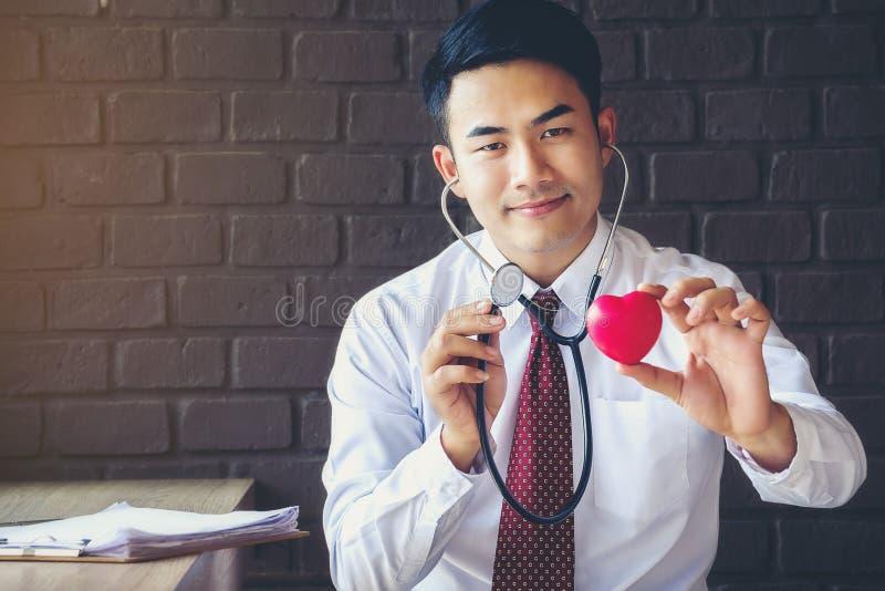 Arts een rode hart en stethoscoop een gecontroleerd houden die, Gezond en royalty-vrije stock foto