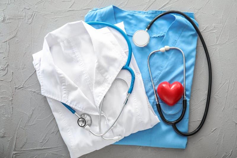 Arts eenvormig met stethoscoop en rood hart op grijze lijst Het concept van de gezondheid royalty-vrije stock foto's