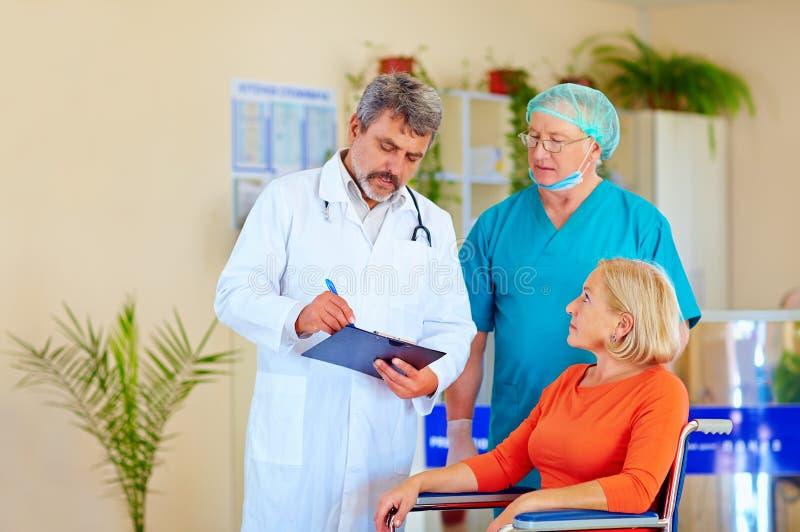 Arts en chirurg raadplegende patiënt over medicijn stock foto