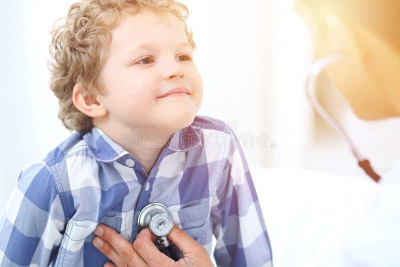 Arts en kind patiënt De arts onderzoekt weinig jongen door stethoscoop Geneeskunde en van de kinderen` s therapie concept stock afbeeldingen