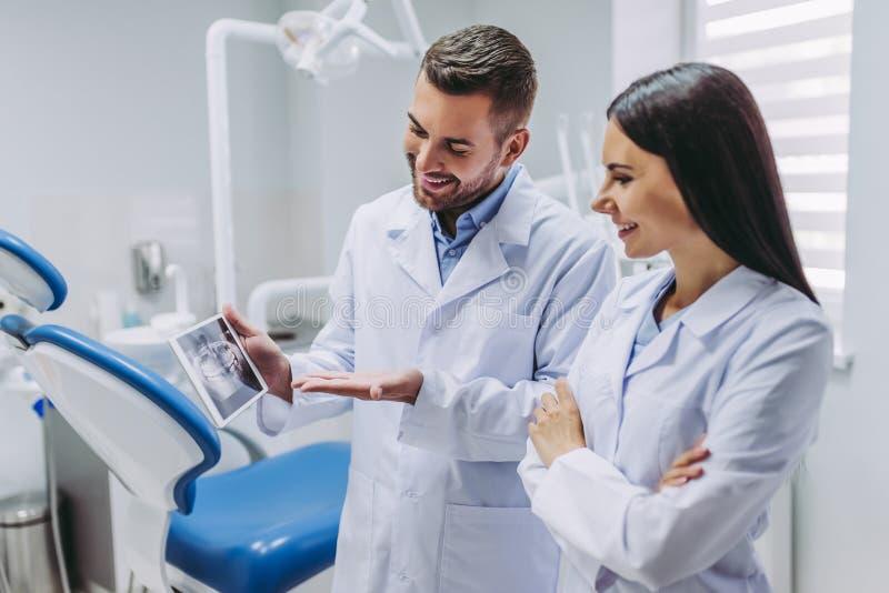 Arts en medewerker die het tabletscherm bekijken stock afbeelding