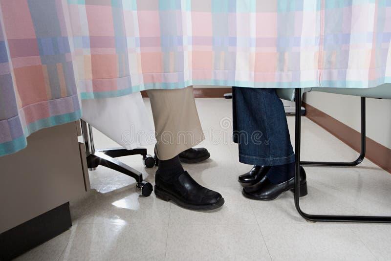 Arts en patiënt achter gordijn royalty-vrije stock afbeelding