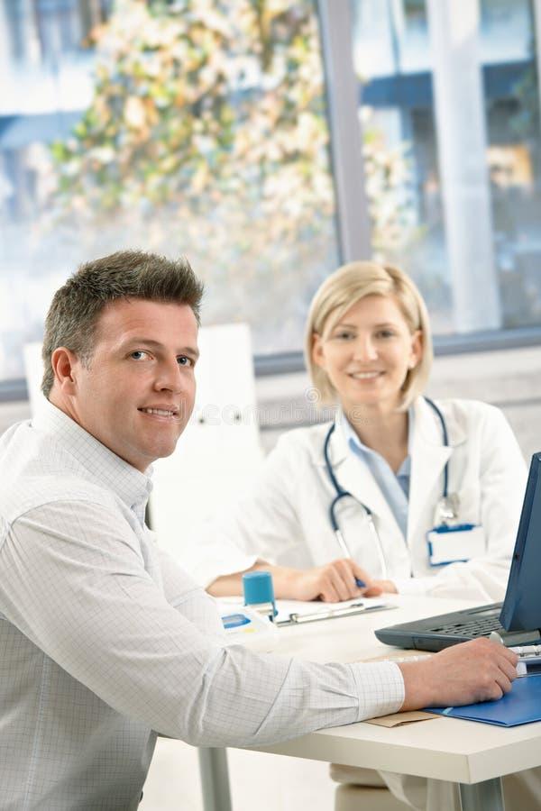 Arts en patiënt in bureau stock foto's