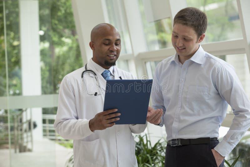 Arts en patiënt die beneden en medisch dossier in het ziekenhuis bespreken kijken royalty-vrije stock fotografie