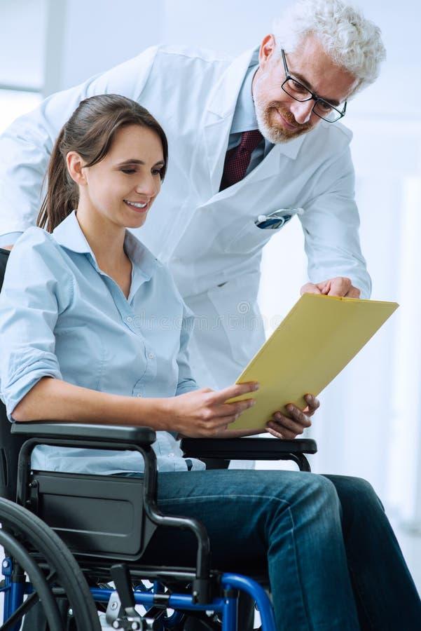 Arts en patiënt die medische dossiers onderzoeken stock fotografie