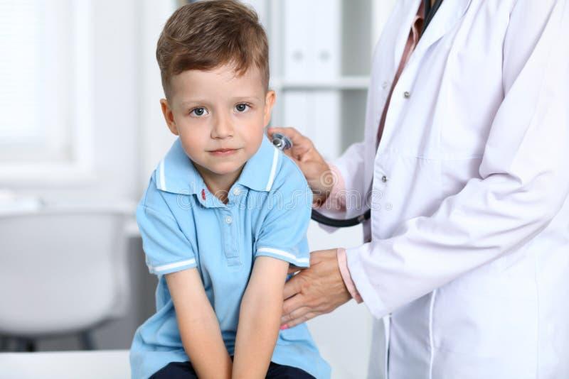Arts en patiënt in het ziekenhuis Gelukkig weinig jongen die pret hebben terwijl wordt onderzocht met stethoscoop gezondheidszorg royalty-vrije stock afbeeldingen