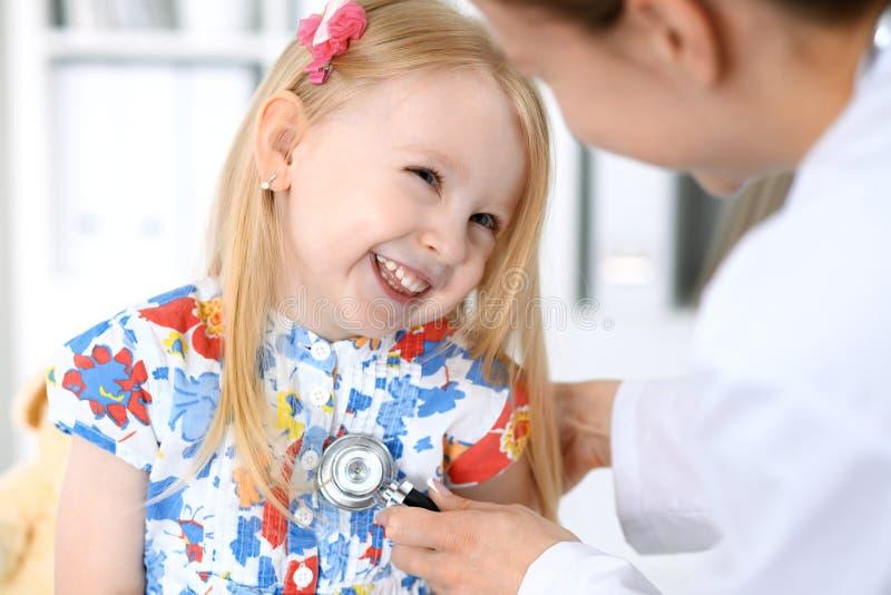 Arts en patiënt in het ziekenhuis Kind die door arts met stethoscoop worden onderzocht stock afbeeldingen