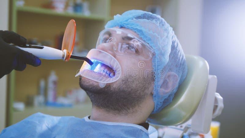 Arts en patiënt met retractor in het tandbureau, die met ultraviolet licht en het oranje beschermende scherm schoonmaken stock afbeelding
