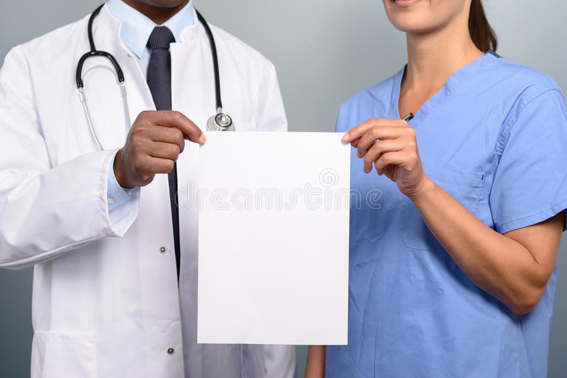 Arts en verpleegster die een leeg wit teken steunen stock foto's