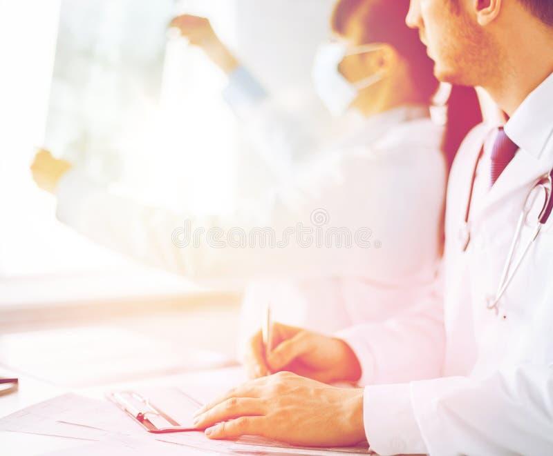 Arts en verpleegster die röntgenstraal onderzoeken stock afbeelding