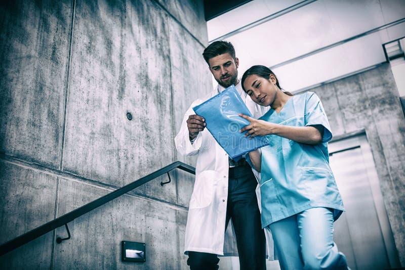 Arts en verpleegster die rapport bekijken terwijl het beklimmen onderaan treden stock foto