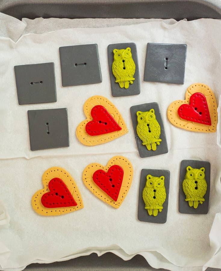 Arts et boutons et coeurs de hibou d'argile de polymère de métier prêts pour la cuisson photographie stock
