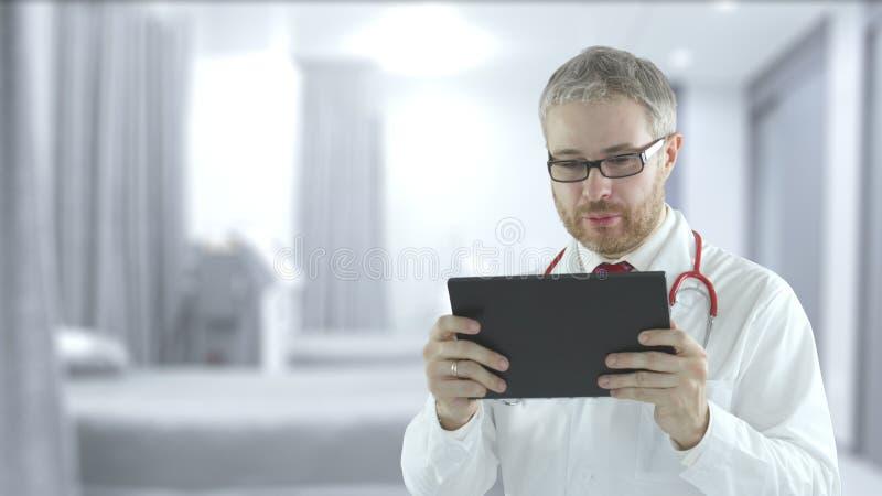 Arts gebruikt moderne tablet-pc voor telegeneeskunde bij een patiënt stock foto
