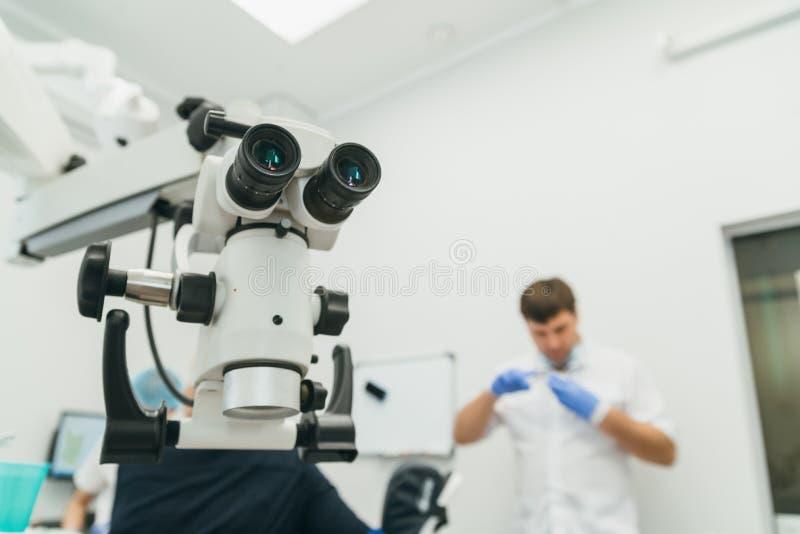 Arts gebruikte microscoop De tandarts behandelt patiënt in modern tandbureau De verrichting wordt uitgevoerd gebruikend kistdam stock fotografie