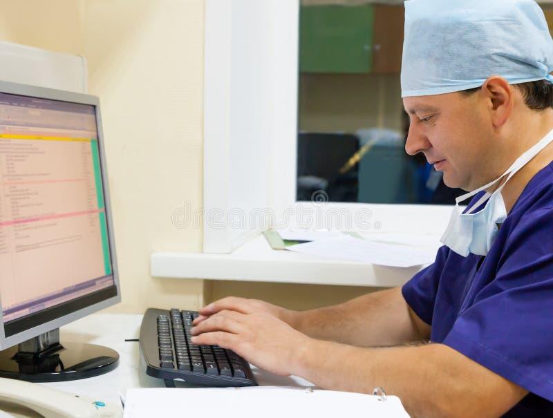Arts die met computertoetsenbord en monitor werken stock afbeelding