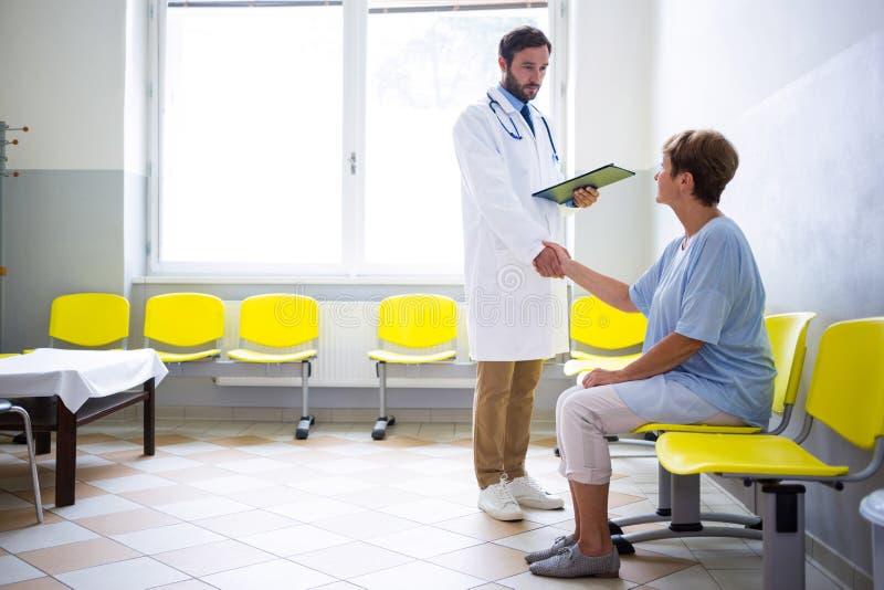 Arts het schudden hand met patiënt in wachtkamer royalty-vrije stock foto's