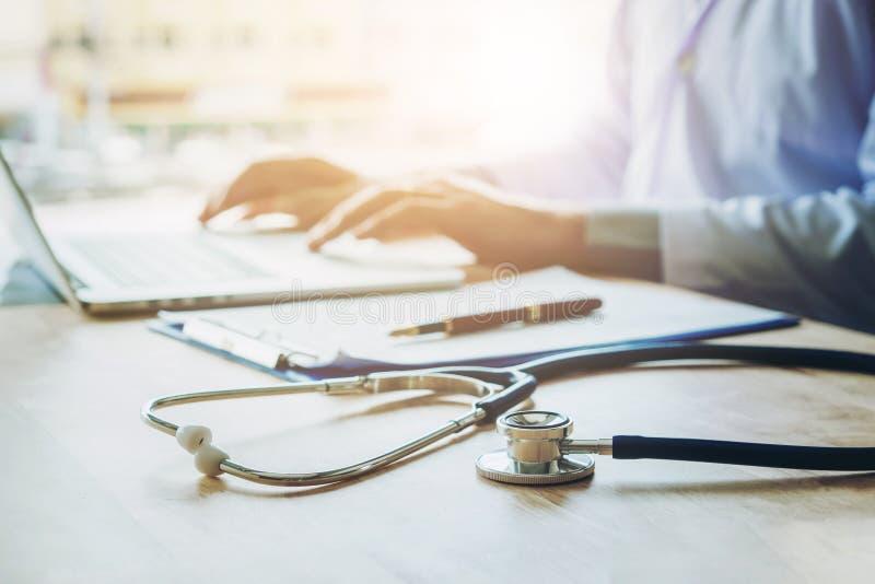 Arts het typen informatie over Laptop in de nadruk van het het Ziekenhuisbureau  stock foto