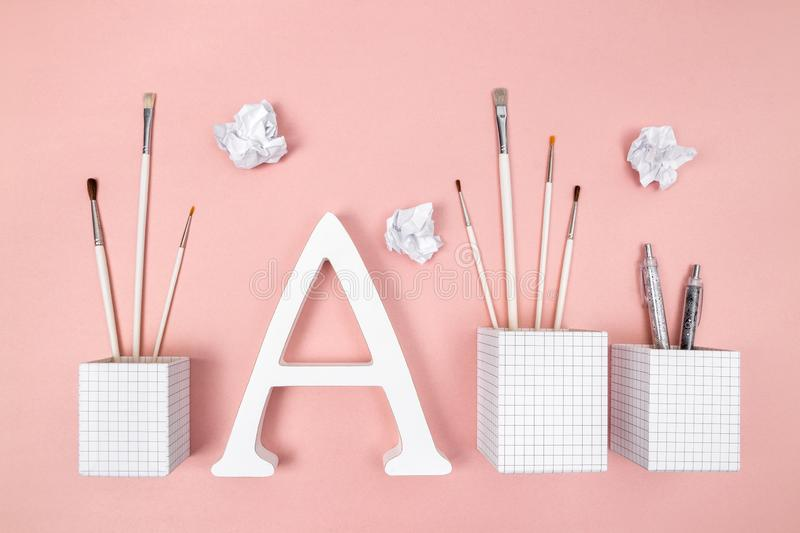 Arts, learning and creativity. Paintbrushes, letter A and crumpled paper, on pastel pink background stock photos