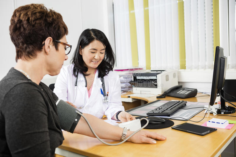 Arts Looking At Patient terwijl het Onderzoeken van Haar Bloeddruk royalty-vrije stock foto's