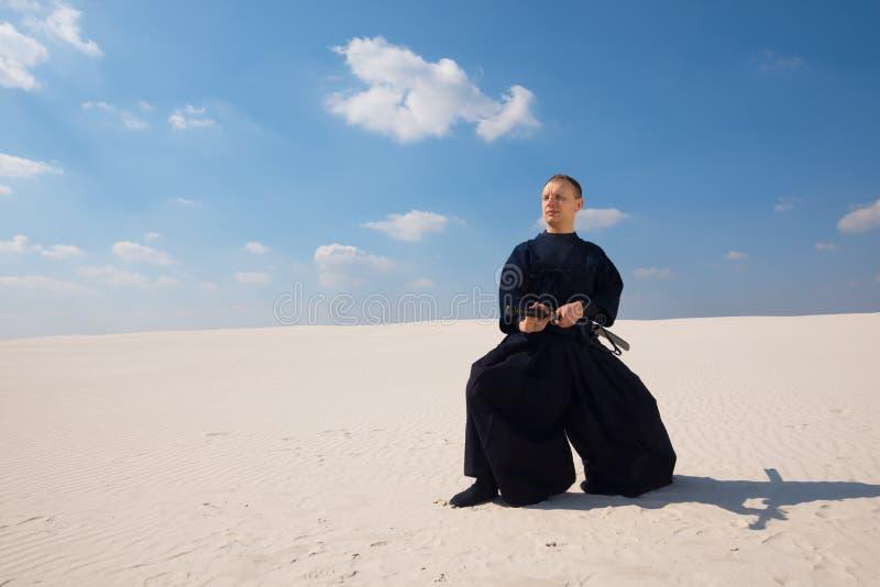 Arts martiaux de pratique d'homme calme dans un désert image libre de droits