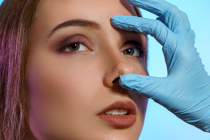 Arts in medische handschoenen meet de neus met vingers op het gezicht van een mooi jong meisje Klinisch onderzoek van plastische  stock foto