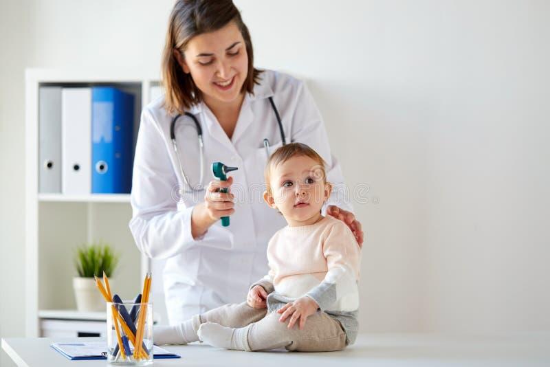 Arts met baby en oorspiegel bij kliniek royalty-vrije stock afbeeldingen
