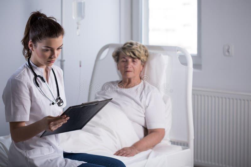 Arts met bejaarde armenhuispatiënt stock afbeeldingen