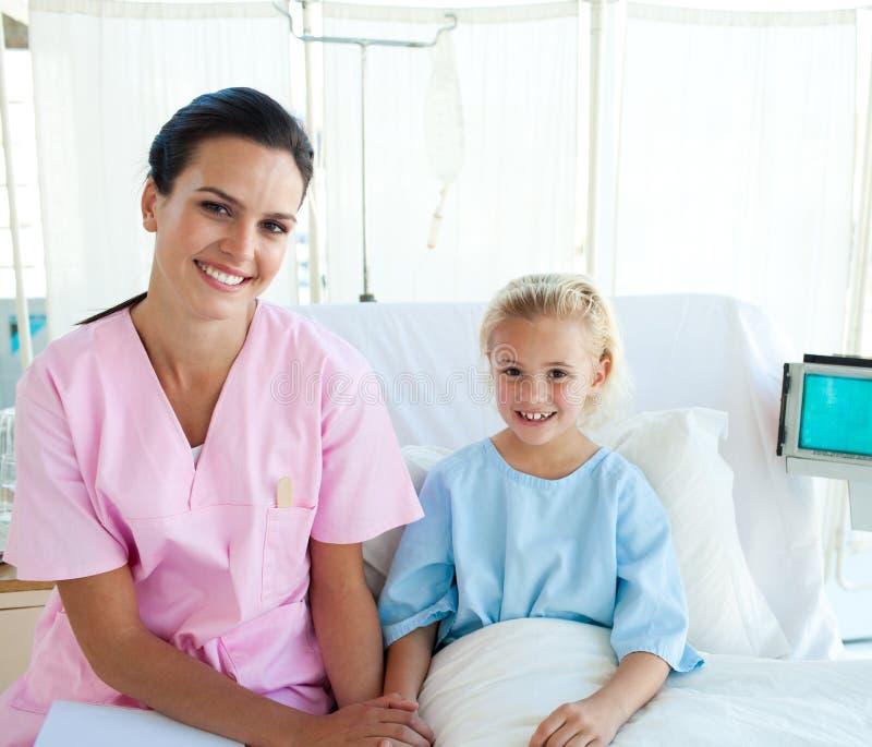 Arts met haar geduldige zitting op een het ziekenhuisbed stock afbeeldingen