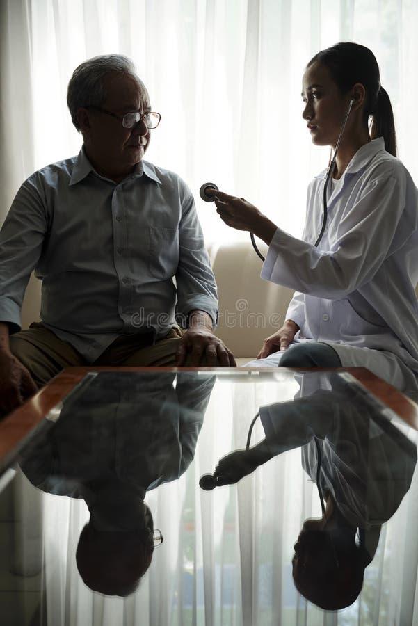 Arts met hogere patiënt thuis royalty-vrije stock foto