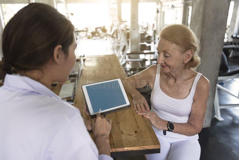 Arts met hogere vrouw in revalidatiecentrum Persoonlijke trainer die iets op Tablet tonen stock fotografie