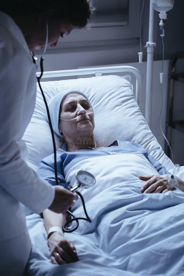 Arts met stethoscoop die de geduldige druk van ` s in hosp meten stock foto