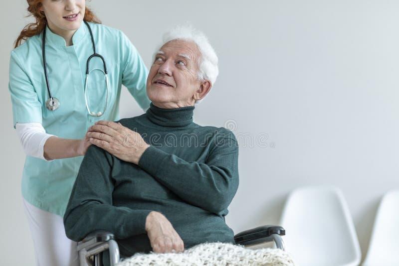 Arts met stethoscoop ondersteunend de gehandicapte hogere mens in een whee royalty-vrije stock afbeelding