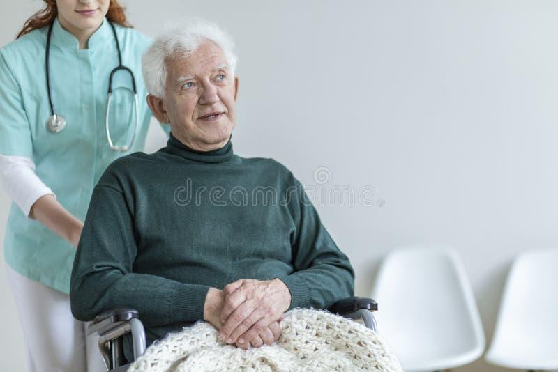Arts met stethoscoop ondersteunend de zieke hogere mens in wheelc stock afbeeldingen