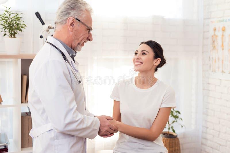Arts met stethoscoop met vrouwelijke patiënt in bureau De arts troost vrouw stock afbeeldingen