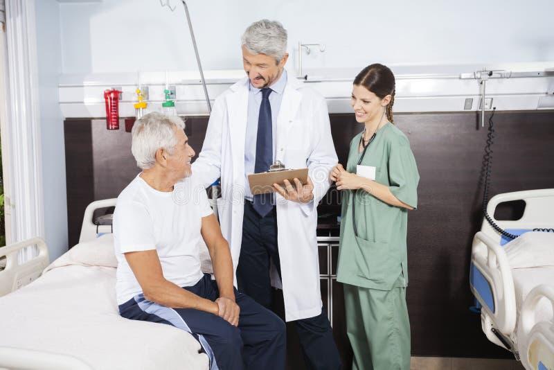 Arts And Nurse Looking bij Patiënt op Rehab-Centrum royalty-vrije stock afbeeldingen