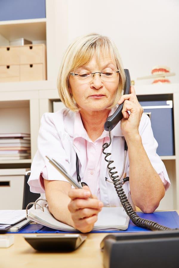 Arts op vraag in haar bureau stock afbeelding