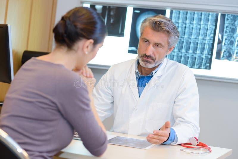 Arts in overleg met vrouwen ernstige uitdrukking stock foto
