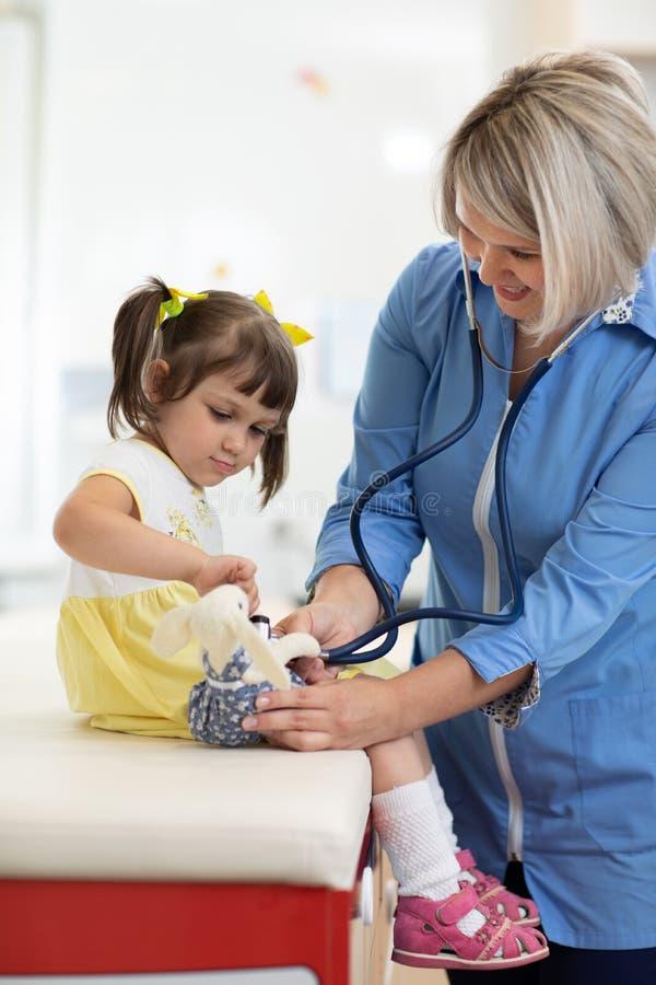 Arts stuk speelgoed onderzoeken en meisje die stethoscoop met behulp van stock afbeelding