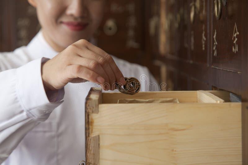 Arts Taking Herb Used voor Traditionele Chinese Geneeskunde uit een Lade stock afbeeldingen