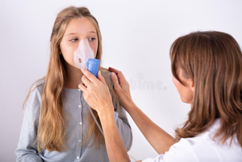 Arts Using Inhaler Mask op Meisje stock foto's